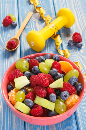 Fresh fruit salad, tape measure and dumbbells for using in fitness, concept of sport, diet, slimming, concept of healthy lifestyles and nutrition Stock fotó