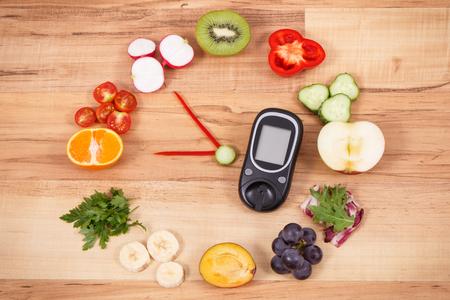 Glucómetro para comprobar el nivel de azúcar y el reloj de frutas y verduras, desayuno saludable para el concepto de diabéticos Foto de archivo