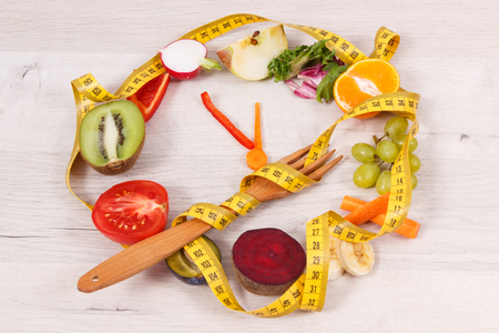 Centimeter with fresh ripe fruits and vegetables in shape of clock showing time to healthy eating and slimming