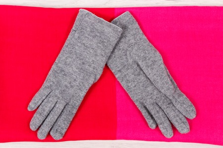 Pair of warm womanly woolen gloves and shawl for using in autumn or winter Stock Photo