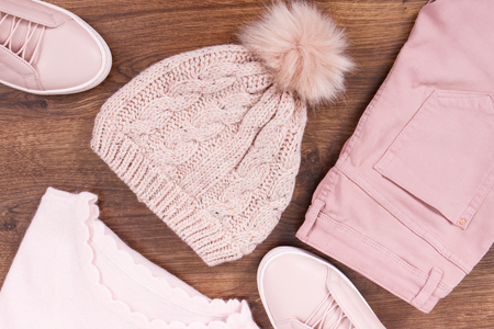 Pink leather shoes, pants, woolen cap and sweater for woman lying on rustic board