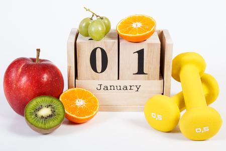 Date January 1 on cube calendar, fresh fruits and dumbbells for fitness, new years resolutions of healthy lifestyle concept