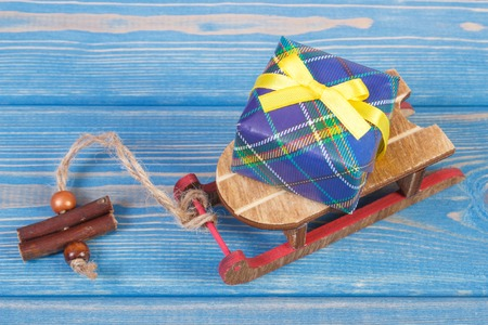 Wooden sled and wrapped colorful gift for Christmas or other celebration lying on old boards