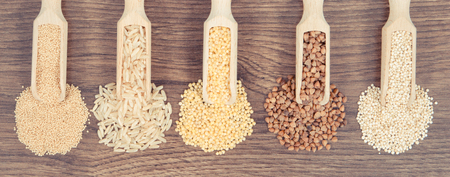 Vintage photo, Various groats, brown rice, amaranth and quinoa seeds on rustic board, concept of healthy, gluten free food and nutrition