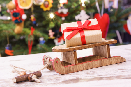 Wrapped gift with ribbon on wooden sled for Christmas and christmas tree with lights and decoration in background, festive time concept