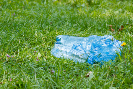 Crushed plastic bottles of mineral water on grass in park