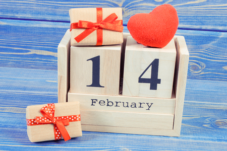 Vintage photo, February 14 on cube calendar, wrapped gifts with ribbon and red heart, decoration for Valentines day