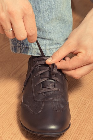 Tying shoelaces of brown casual comfortable leather shoe, male footwear concept 免版税图像