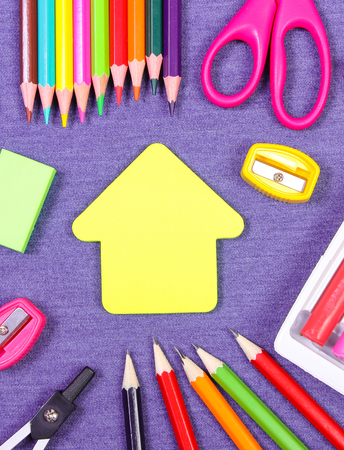 School and office supplies on jeans background, shape of building