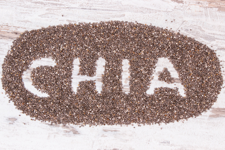 Inscription chia and heap of seeds, concept of healthy food containing natural vitamins, minerals and dietary fiber