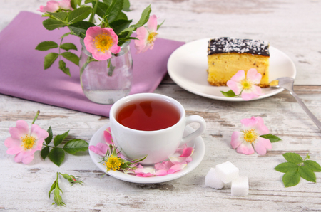 Cup of hot tea with wild rose, blooming flowers and cheesecake on plate on rustic board