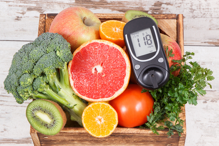 Glucose meter with natural healthy fruits and vegetables. Concept of checking sugar level, diabetes, diet and slimming