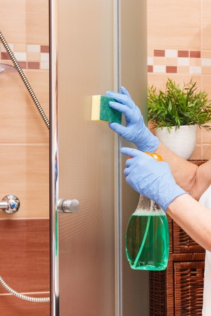 Hand of senior woman in protective gloves with sponge and detergent cleaning glass shower door, concept of household duties Zdjęcie Seryjne