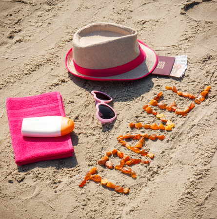 Inscription travel made of amber stones, accessories for sunbathing and passport with currencies euro at beach