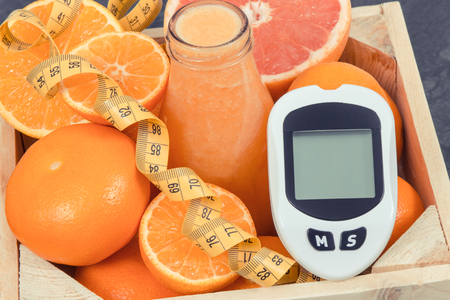 Glucose meter for measuring sugar level, freshly blended coctail from citrus fruits and centimeter. Diabetes, slimming, diet and healthy nutrition concept