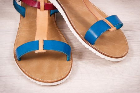 Pair of womanly leather sandals on white board, concept of footwear for using on holiday Reklamní fotografie