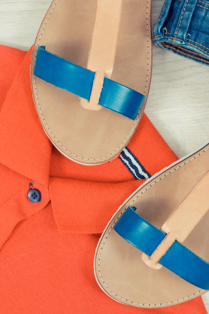 Fashionable and comfortable leather sandals, blue jeans and red cotton shirt or sweater for woman