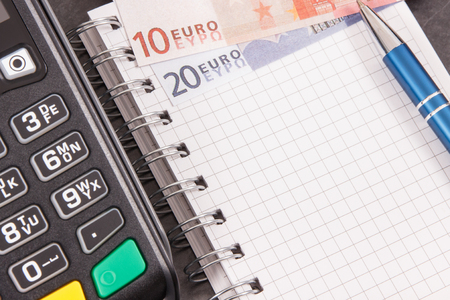 Credit card reader for cashless payment transaction, notepad for writing notes and euro. Finance and business concept Imagens