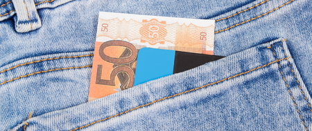 Money and credit card in pocket of blue pants. Finance and banking concept Stok Fotoğraf