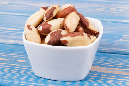 Heap of brazil nuts in glass bowl on old boards, healthy nutrition concept Standard-Bild - 124516440
