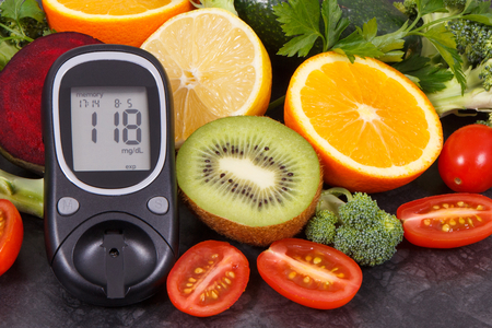 Glucometer with result of measurement sugar level and fresh fruits with vegetables, diabetes and nutritious dessert containing healthy minerals and vitamins