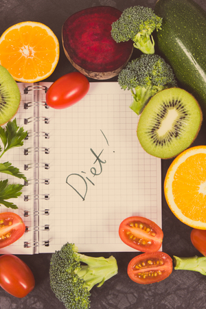 Notepad and fresh ripe fruits with vegetables containing natural vitamins and minerals, slimming and diet concept Stock Photo - 124516587