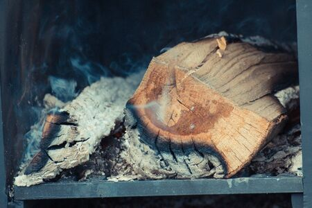 Burning firewood, carbon and ash in fireplace or smokehouse
