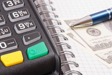 Payment terminal, notepad for writing notes and money. Business concept