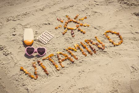 Medical pills, inscription vitamin D made of amber stones and accessories for sunbathing at beach, concept of vacation time and prevention of vitamin D deficiency