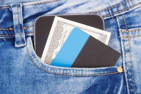 Creditcard, valuta's dollar en smartphone vooraan jeanszak. Concept van contante of contante betaling Stockfoto