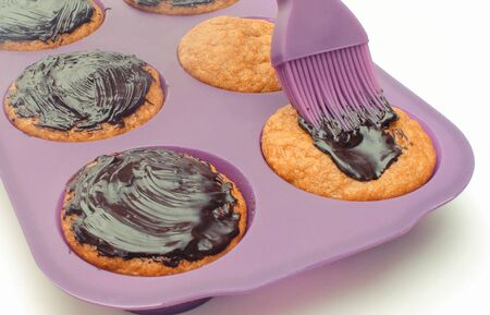 Fresh baked carrot muffins in silicone mold and pouring sweet chocolate. Delicious dessert concept