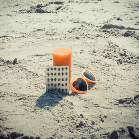 Medical pills, carrot juice and sunglasses at beach, concept of prevention of vitamin A deficiency, beautiful and lasting tan