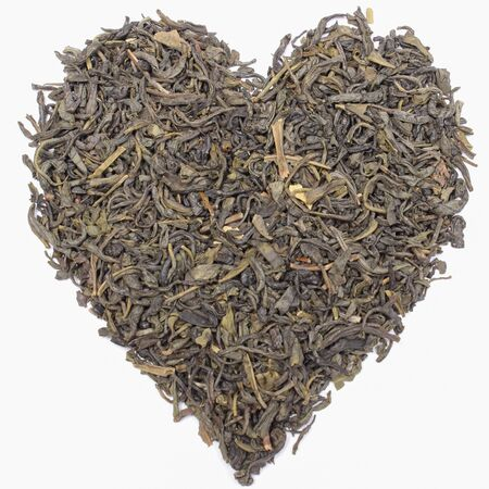 Closeup of dried green tea in shape of heart on white background. Healthy lifestyles