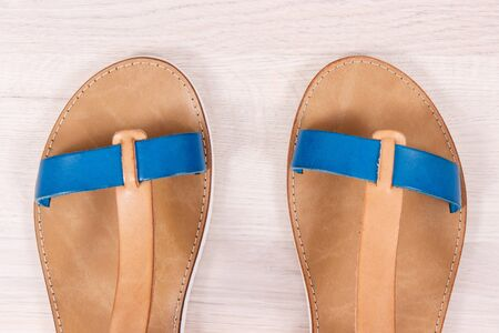 Pair of womanly leather sandals on white board, concept of footwear for using on holiday 版權商用圖片