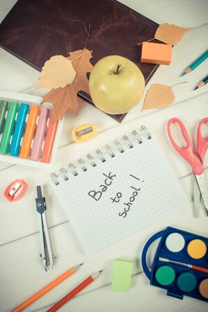 Book, fresh apple and school accessories on white boards, inscription back to school in notepad