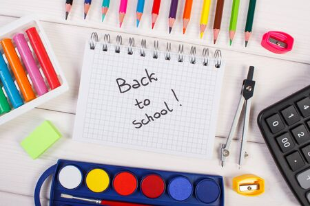 School and office accessories on white boards. Inscription back to school in notepad