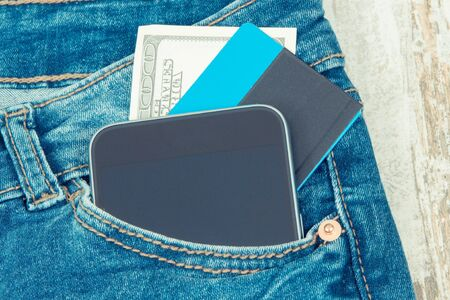 Credit card, money and mobile phone in front jeans pocket. Concept of cashless or cash paying for shopping