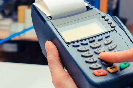 Hand der Frau, die das Zahlungsterminal im Elektrofachgeschäft benutzt, mit Kreditkarte bezahlt, persönliche Identifikationsnummer eingeben
