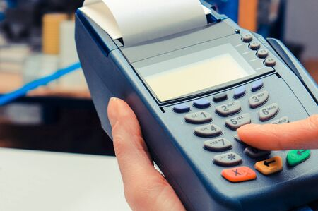 Hand of woman using payment terminal in electrical shop, paying with credit card, enter personal identification number