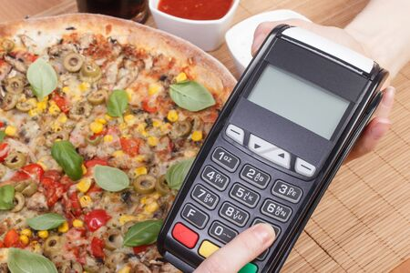 Using payment terminal, enter personal identification number, cashless paying for vegetarian pizza in restaurant, finance and banking concept