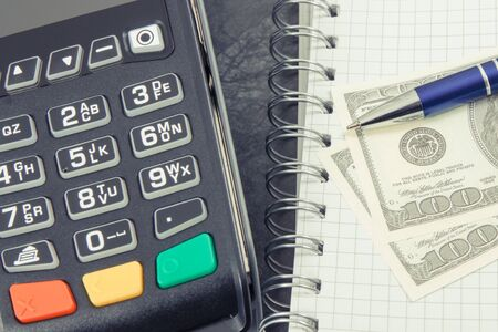 Payment terminal using for cashless paying in different places, notepad for notes and currencies dollar Фото со стока
