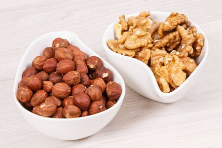 Hazelnuts and walnuts in white bowl as source healthy natural vitamins and minerals, nutritious eating concept