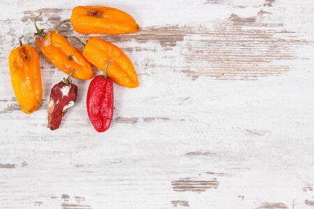 Old wrinkled moldy peppers on old rustic board, concept of unhealthy and disgusting vegetable. Place fo text
