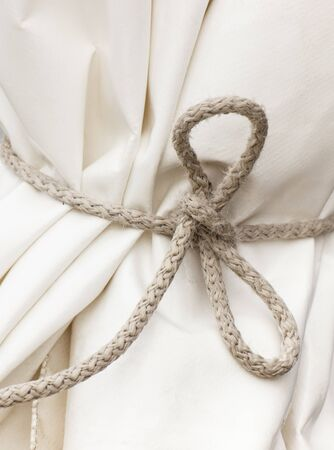 Closeup of waterproof white tarpaulin or curtain tied string or cord Stock Photo