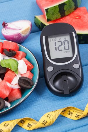 Glucose meter for measuring sugar level and fresh prepared salad of watermelon with feta cheese as source healthy natural minerals Stock Photo