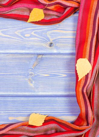 Frame of shawl for woman and autumnal leaves on boards. Warm clothing for autumn or winter, copy space for text Stok Fotoğraf