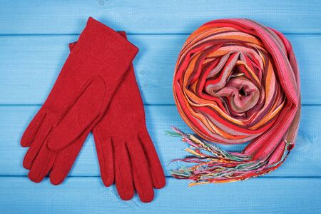 Gloves and colorful shawl for woman on boards. Clothing for autumn or winter, womanly accessories