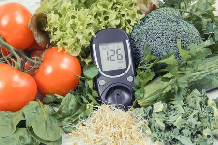 Glucometer for measuring sugar level and vegetables with sprouts as healthy nutritious food during diabetes containing vitamins and minerals Stock fotó