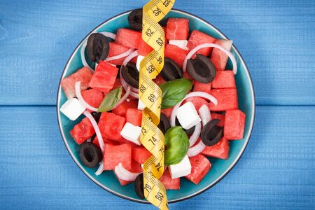 Fresh summer salad of watermelon with feta cheese and tape measure. Slimming, healthy lifestyles and nutrition concept Stock Photo