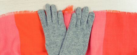 Gloves and shawl on white board, concept of warm womanly clothing for autumn or winter